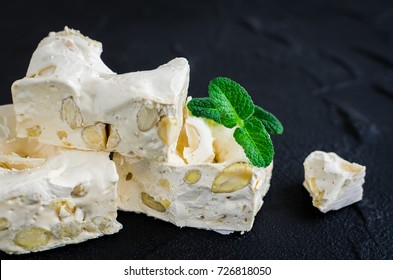 Delicious traditional Italian festive torrone or nougat with nuts on black stone background. Soft nougat blocks with almonds with fresh mint leaves. Holiday concept. Italian sweets.