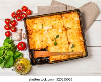 Delicious traditional italian lasagna  with ingredients served on white  wooden table, top view