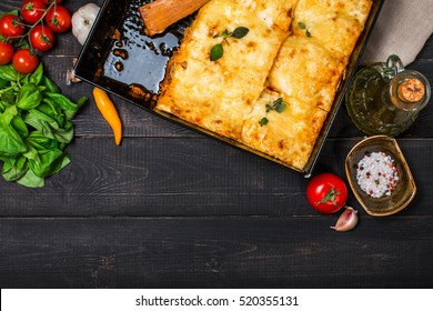 Delicious traditional italian lasagna  with ingredients served on dark rustic  wooden table, top view