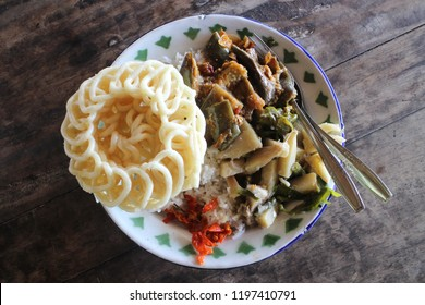 Delicious traditional lunch set menu of Indonesian, it's containing of rice, vegetables, chili, and kerupuk crackers in a white metal plate that set on the dark brown wooden table