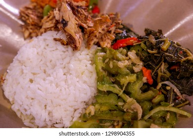 Delicious traditional street food of Jakarta: rice with bitter melon and papaya leaves as vegetable.