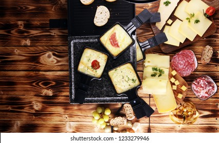 Delicious traditional Swiss melted raclette cheese served in individual skillets with salami