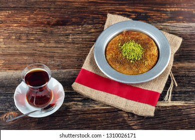 Delicious traditional Turkish dessert, Kunefe with pistachio and tea.