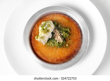 Delicious traditional Turkish dessert kunefe with pistachio powder over white background