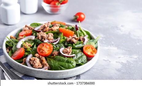 Köstlicher Thunfischsalat mit Tomaten, roten Zwiebeln und Spinat. Gesunde und diätetische Ernährung Speicherplatz kopieren