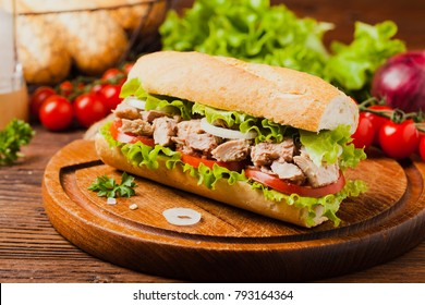Delicious tuna sandwich, served with lettuce, tomato and onion. Natural wood in the background. Front view.