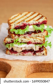 Delicious Turkey or chicken sandwich with brie or Camembert cheese, lettuce and cranberry (lingonberry, cowberry) chutney on grain bread with flax seed. Gourmet Breakfast. Panini. Selective focus