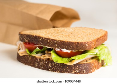 Delicious turkey sandwich with lettuce, mayonnaise and tomato from brown bag lunch