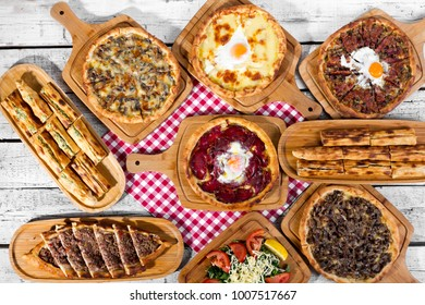 Delicious Turkish and Arabic Traditional Ramadan Food Pide, Lahmacun and Turkish Pizza serving on rustic white wood background. Round, thin piece of dough topped with minced meat, vegetables and herbs