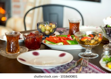 Delicious Turkish, Greek and Arabic Breakfast serving sliced black and green olive oil, black tea, tomato, cucumber, fried borek, arugula, bread and strawberry ham on table with fireplace background.
