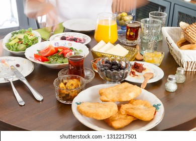 Delicious Turkish, Greek and Arabic Breakfast serving sliced black and green olive oil, black tea, tomato, cucumber, fried borek, arugula, bread and strawberry ham on table with fresh orange juice.