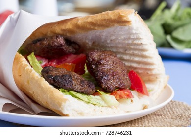 Delicious Turkish Meatballs Sandwich, Kofte Ekmek. Ingredients with bread crumbs, butter, sliced onion, cucumber, tomato, lettuce salad, pickles and seasoning spices. Hamburger serving on blue table.