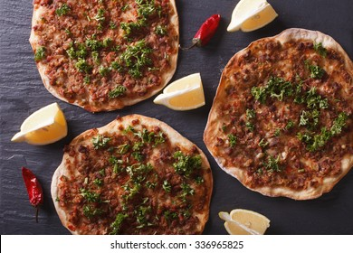 Delicious Turkish pizza lahmacun closeup on a stone table. Horizontal top view