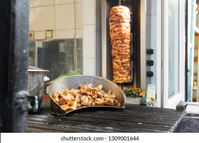 Delicious turkish skewered fast food chicken doner kebab, shawarma meat cooking and turning side by side on rotating spit Arab Middle Eastern or Mediterranean style. Selective focus.