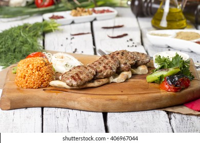 Delicious Turkish Traditional Kebab Kofte with vegetables on wood plate (meatballs)