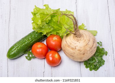 Delicious turnip, cucumber, tomato and parsley ingredients on a vitamin salad on a white wooden background