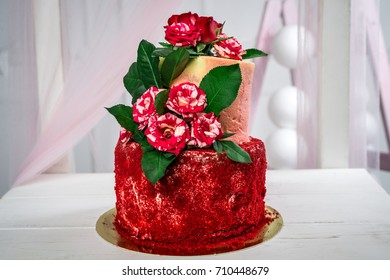 A delicious two-tier handmade cake decorated with red flowers.