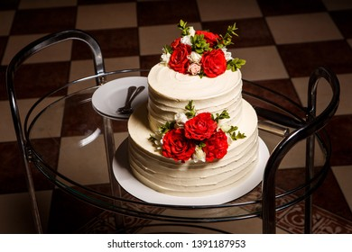 delicious two-tiered white creamy wedding cake with red and pink roses served on glass tray with plates and spoons