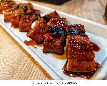 Delicious Unagi Eel Nigiri Sushi (Eel Sushi) on white plate. Traditional Japanese cuisine. Close up of Unagi Sushi Set Japan eel.
