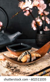 Delicious Unagi Eel Nigiri Sushi (Eel Sushi) . Dish decorated with a sprig of cherry blossoms. Traditional Japanese cuisine
