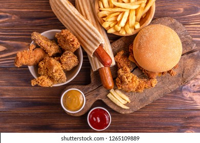 Delicious but unhealthy food with ketchup and mustard on vintage cutting board. Fast carbohydrates, junk and fast food. Warm wooden background.