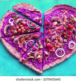 Delicious unusual vegan pizza in a shape of heart with mushrooms, chickenpeas with beet base, unusual colors