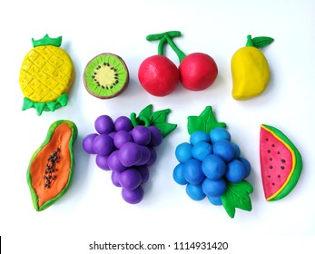 Delicious variety fruits made from plasticine clay on white background, colorful pineapple kiwi cherry mango papaya grapes blueberry watermelon shaped dough