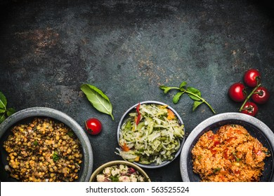 Delicious various vegetarian salads in bowls on dark rustic background, top view, border. Healthy eating, Vegetarian or vegan food concept