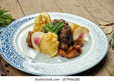 Delicious veal (beef) cheeks with honey sauce and mashed potato garnish in a blue plate on a wooden background. Close up view