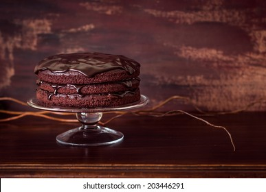 Delicious vegan chocolate cake on vintage wooden table. Selective focus. Copy space for your text.