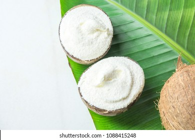 Delicious Vegan Ice Cream in Coconut Bowls on Large Green Palm Leaf on White Marble Stone Tabletop. Plant Based Diet Healthy Superfoods Desserts Tropical Vacation Concept. Copy Space