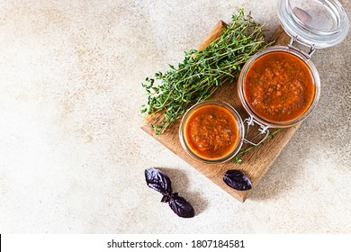 Delicious vegetable caviar in jars, thyme and purple basil on wooden board, light stone background. Homemade caviar with eggplant, tomatoes and bell pepper. Top view, copy space.