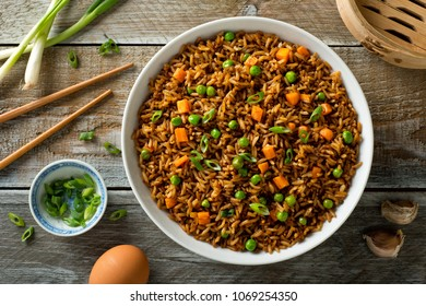 Delicious vegetable fried rice with egg, carrot, garlic, green peas and scallions.