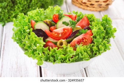 Delicious vegetable salad with tomato, cucumber, onion, olives, basil.