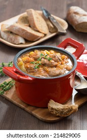 delicious vegetable stew with sausages in a pan, vertical, top view