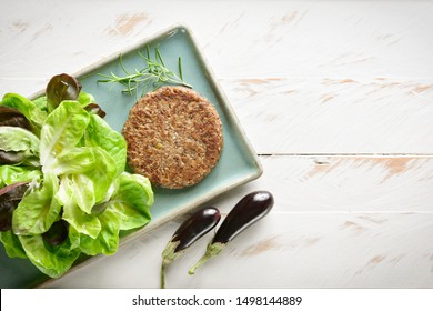 Delicious vegetarian burger served on a blue porcelain plate with lettuce salad aside, on a white wooden table. Ready to eat and serve.
