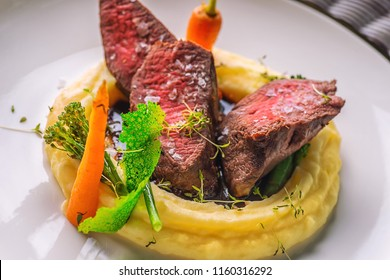 delicious venison steak with potatoes mash and vegetables on white plate, product photography for exclusive restaurant