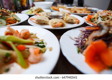 Delicious Vietnam cuisine menu in exotic food restaurant.Fried crispy shrimp rolls on white plate.Fresh colorful vegetable salads,sea food in Chinese cafe.Asian gourmet snacks