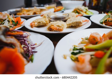Delicious Vietnam cuisine menu in exotic food restaurant.Focus on fried crispy shrimp rolls on white plate.Fresh colorful vegetable salads & sea food in Chinese cafe.Asian gourmet snacks