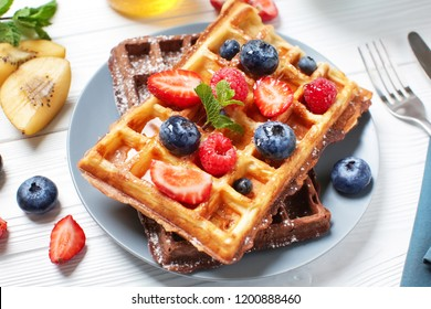 Delicious waffles with berries on plate