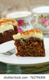 Delicious walnut and carrot cake with marzipan icing on white plate, closeup