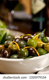 Delicious Warm Olives with Citrus Zest tossed in olive oil and herbs served in a white dish
