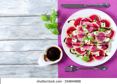 delicious watermelon radish salad with mozzarella, onion chives and basil on the white dish with caramelized balsamic vinegar in the gravy boat, top view
