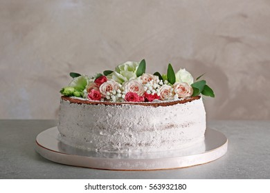 Delicious wedding cake on table and grey textured background