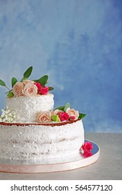 Delicious wedding cake on table and blue textured background