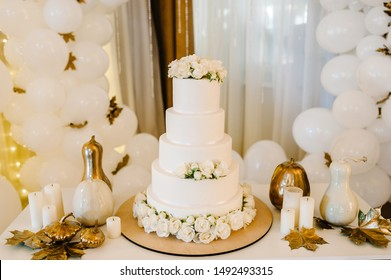 Delicious wedding reception. Cake on a background balloons. Decorated table for wedding. White balloons, candles, autumn leaves and pumpkins. Autumn location and Halloween decor. Birthday party.