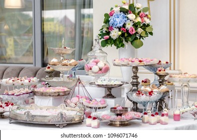 Delicious wedding reception candy bar dessert table full with cakes and sweets and a flower vase with hydrangeas.