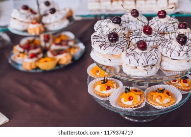 Delicious wedding reception candy bar dessert table. A lot of alcohol and glasses. Coktails and sweets. Wedding party table.
