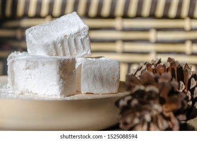 Delicious white traditional bulgarian turkish delight on wooden dish sprinkled with icing sugar like snow. Oriental sweets for tea, next to pine cones. Winter Christmas dessert in the bright sunshine.