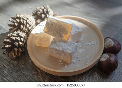 Delicious white traditional turkish delight on wooden dish sprinkled with icing sugar. Oriental sweets next to pine cones and chestnut nuts closeup. Winter Christmas dessert in the bright sunshine.